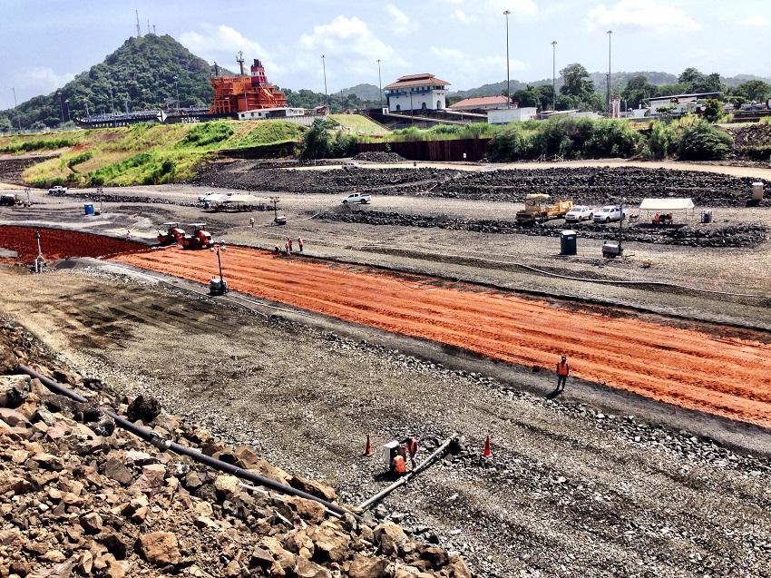 la presa en construcción que divide el nuevo Canal del existente al fondo un barco haciendo el esclusaje en Pedro Miguel